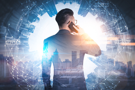 The double exposure image of the businessman using a smartphone during sunrise overlay with cityscape image. The concept of modern life, business, city life and internet of things. Banco de Imagens