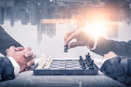 double exposure image of both businessmen playing the chess board game and overlay with cityscape image. the concept of accounting, business, financial, economy and investment. Banco de Imagens