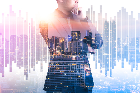 The double exposure image of the businessman thinking during sunrise overlay with cityscape and business chart image. The concept of modern life, business, city life and internet of things.