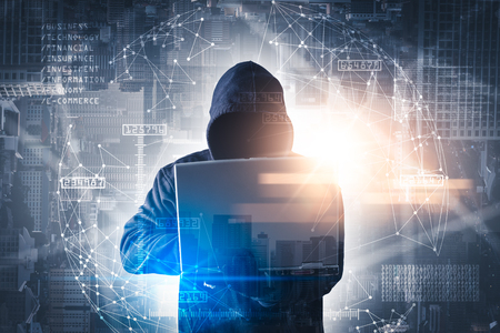 The double exposure image of the hacker using a laptop overlay with binary code image and blurred cityscape is backdrop. the concept of cyber attack, virus, malware, and cyber security. Reklamní fotografie