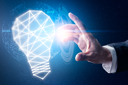 The abstract image of the hand point to the illumination lamp. the concept of communication, idea, futuristic, internet of things and technology.