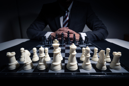 the abstract image of the businessman looking at the chess board and thinking during the chess game. the concept of intelligence and education.