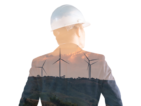 The double exposure image of the engineer standing back during sunrise overlay with wind turbine image. The concept of engineering, power, electricity, environment and future. Banco de Imagens