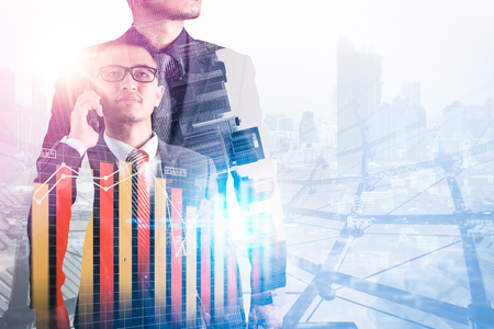 The double exposure image of the businessman using a smartphone during sunrise overlay with cityscape and business chart image. The concept of modern life, business, city life and internet of things. Banco de Imagens