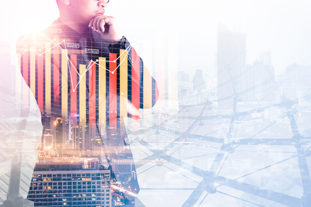 The double exposure image of the businessman thinking during sunrise overlay with cityscape and business chart image. The concept of modern life, business, city life and internet of things