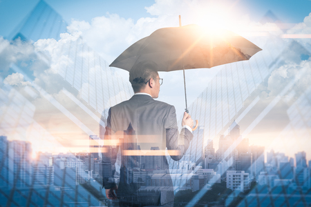 The double exposure image of the Businessmen are spreading umbrella during sunrise overlay with cityscape image. The concept of modern life, business, insurance and protection.
