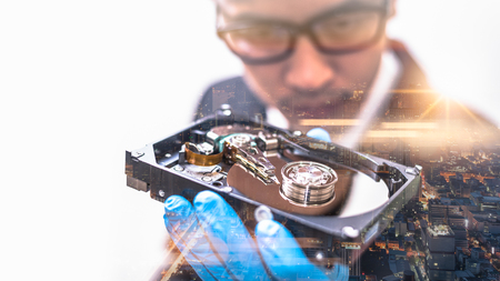the double exposure image of the businessman hold and looking to inside of hard disk drive overlay with cityscape image. the concept of technology, data and business.