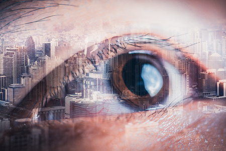 The double exposure image of the businessmans eye overlay with cityscape image. The concept of modern life, futuristic, technology, iris scanner and internet of things. Reklamní fotografie