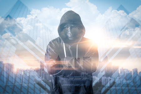 The abstract image of the hacker standing overlay with futuristic hologram and the future cityscape is backdrop. the concept of cyber attack, virus, malware, illegally and cyber security. Reklamní fotografie
