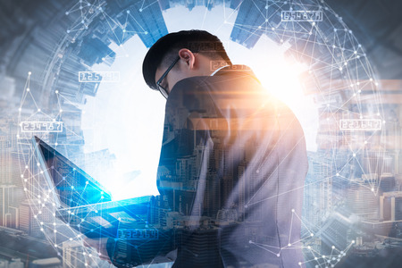 The double exposure image of the business man using a laptop computer during sunrise overlay with cityscape image. The concept of modern life, business, city life and internet of things.