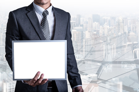 the abstract image of a businessman showing a mock-up whiteboard and cityscape image is the backdrop. the concept of mock-up, business, advertising and message.
