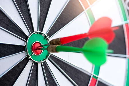 the abstract image of a dartboard laying on the table with darts embroidered. the concept of business, dart board, direction and future.