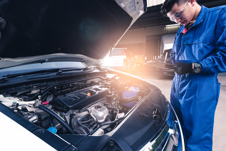 The Asian technician analyzes the cars engine and noting list in the garage. the concept of automotive, repairing, mechanical, vehicle and technology.