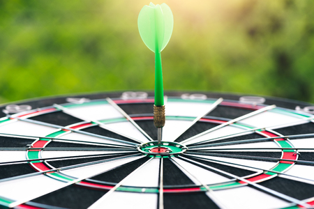 the abstract image of a dartboard laying on the table with darts embroidered, the concept of business, dart board, direction and future.