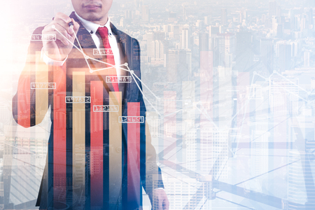 The double exposure image of the businessman point to business chart  overlay with cityscape image. The concept of modern life, business, city life and internet of things