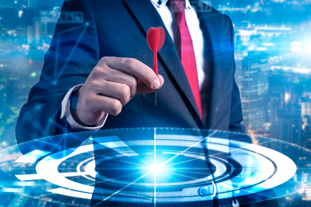 The abstract image of businessman throwing a dart to futuristic target hologram. the concept of business, dart board, direction and future. Reklamní fotografie