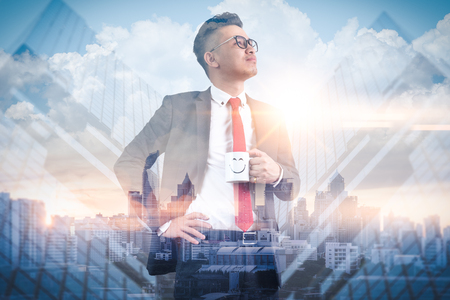The double exposure image of the businessman standing and hold a coffee cup during sunrise overlay with cityscape image. The concept of modern life, business, happiness and future.