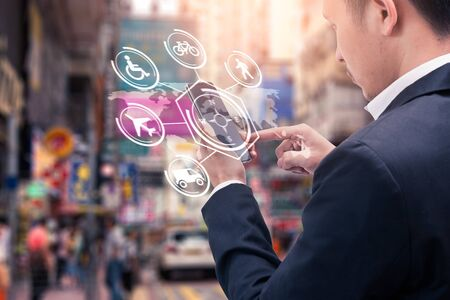 The abstract image of business man point to the hologram on his smartphone and blurred cityscape is backdrop. the concept of communication, transportation, navigation, internet of things and travel.