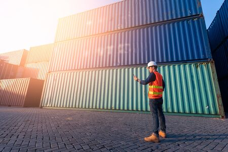 The abstract image of the engineer using a smartphone in shipping container yard and copy space. the concept of engineering, shipping, shipyard, business and transportations. Stock Photo