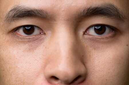 the close up image of the eyes of asian man. The concept of modern life, technology, iris scanner and internet of things