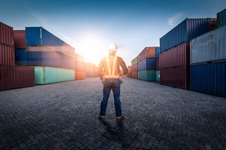 The abstract image of the engineer standing in shipping container yard and copy space. the concept of engineering, shipping, shipyard, business and transportations.
