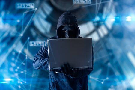 The abstract image of the hacker standing overlay with futuristic hologram and the future cityscape is backdrop. the concept of cyber attack, virus, malware, illegally and cyber security. Stock Photo