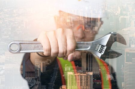 the double exposure image of the engineer hold a wrench overlay with the cityscape image. The concept of engineering, construction, city life and future.