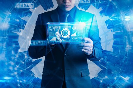 The abstract image of businessman point to the hologram on his smartphone and blurred cityscape is backdrop. the concept of communication network, cyber security, internet of things and future life. Stock Photo