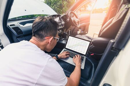 The asian technician analyze the cars engine graph on laptop computer in the garage. the concept of automotive, repairing, mechanical, vehicle and technology.