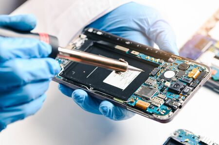 The technician repairing the smartphones motherboard in the lab by soldering method. the concept of computer hardware, mobile phone, electronic, repairing, upgrade and technology. Banco de Imagens