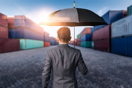 The abstract image of the Businessman is spreading umbrella during sunrise overlay with container yard image. The concept of transportations, business, insurance, and protection. Stock Photo