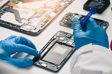 The asian technician repairing the smartphones motherboard in the lab with copy space. the concept of computer hardware, mobile phone, electronic, repairing, upgrade and technology.
