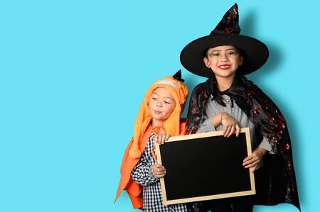the abstract image of the child in the Halloween costume holds the empty blackboard. the concept of Halloween, festival, October, and childhood.