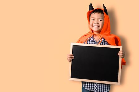 the abstract image of the boy in the Halloween costume holds the empty black board. the concept of Halloween, festival, October, and childhood.