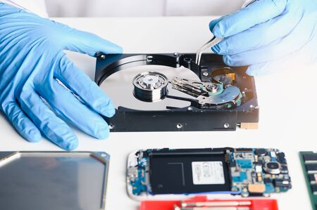 The abstract image of the technician repairing inside of hard disk drive by screwdriver in the lab. the concept of data, hardware, technician and technology