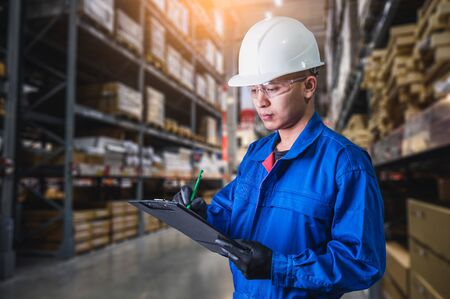 The abstract image of the engineer standing in front of the warehouse storage. the concept of engineering, shipping, management, warehouse and transportations. Stock Photo