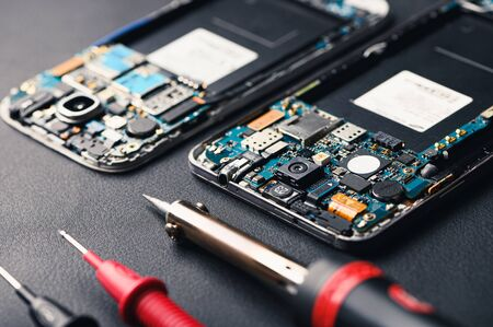 The abstract image of the technician assembling inside of smartphone by screwdriver in the lab. the concept of computer hardware, mobile phone, electronic, repairing, upgrade and technology. Stock Photo