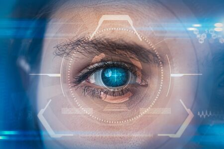 The double exposure image of the businesswoman's eye overlay with futuristic hologram. The concept of modern life, futuristic, technology, iris scanner and internet of things.