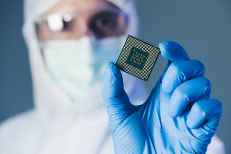 the scientist holding a chipset in the laboratory. the concept of computer, service, electronics, hardware, repairing, upgrade and technology.