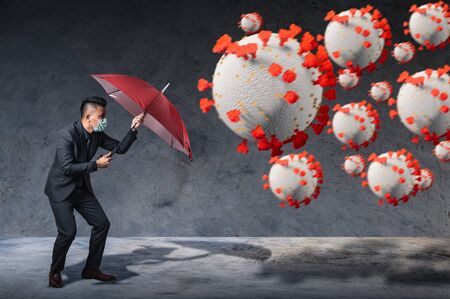 the businessman using an umbrella for defending coronavirus pandemic. the concept of insurance, protection, business and health care.