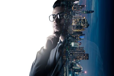 The double exposure image of the businessman thinking overlay with cityscape image and futuristic hologram. The concept of modern life, business, city life and internet of things.