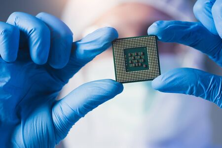 the scientist holding a chipset in the laboratory. the concept of computer, service, electronics, hardware, repairing, upgrade and technology. 免版税图像
