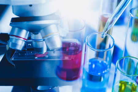 the close up image of the laboratory's tools such as a microscope, test tube laying on the table. the concept of coronavirus, vaccination, laboratory and medical.