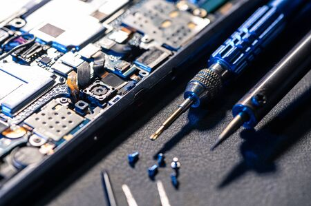 The inside of the smartphone's motherboard and tools lay on the back table. the concept of computer hardware, mobile phone, electronic, repairing, upgrade and technology. 免版税图像