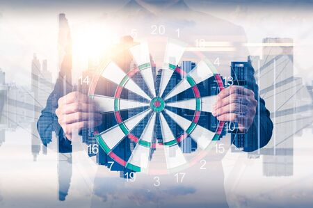 the double exposure image of the businessman holding a dart board and overlay with cityscape image. The concept of strategy, business, destination and success .