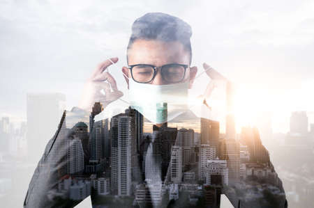 the double exposure image of the businessman wearing the medical mask and overlay with cityscape image. the concept of covit-19, work at home, quarantine, healthcare and business.