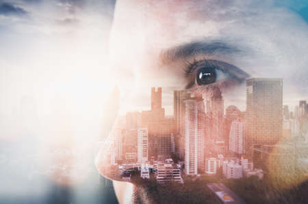 The double exposure image of the businessman looking up during sunrise overlay with cityscape image. The concept of modern life, technology, iris scanner and internet of things