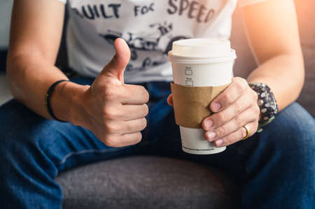 the man holding the recyclable coffee cup and make thumb up