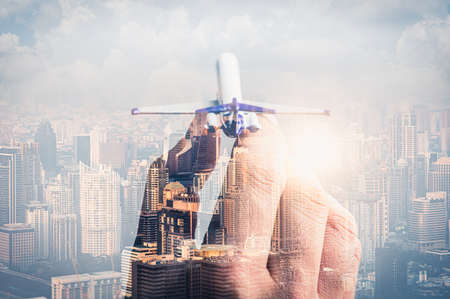 the double exposure image of the airplane model on hand overlay with cityscape image. the concept of travel, business, aircraft, international and transportations.
