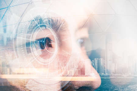 The double exposure image of the businessman looking up during sunrise overlay with cityscape image and futuristic hologram. The concept of modern life, technology, iris scanner and internet of things 免版税图像